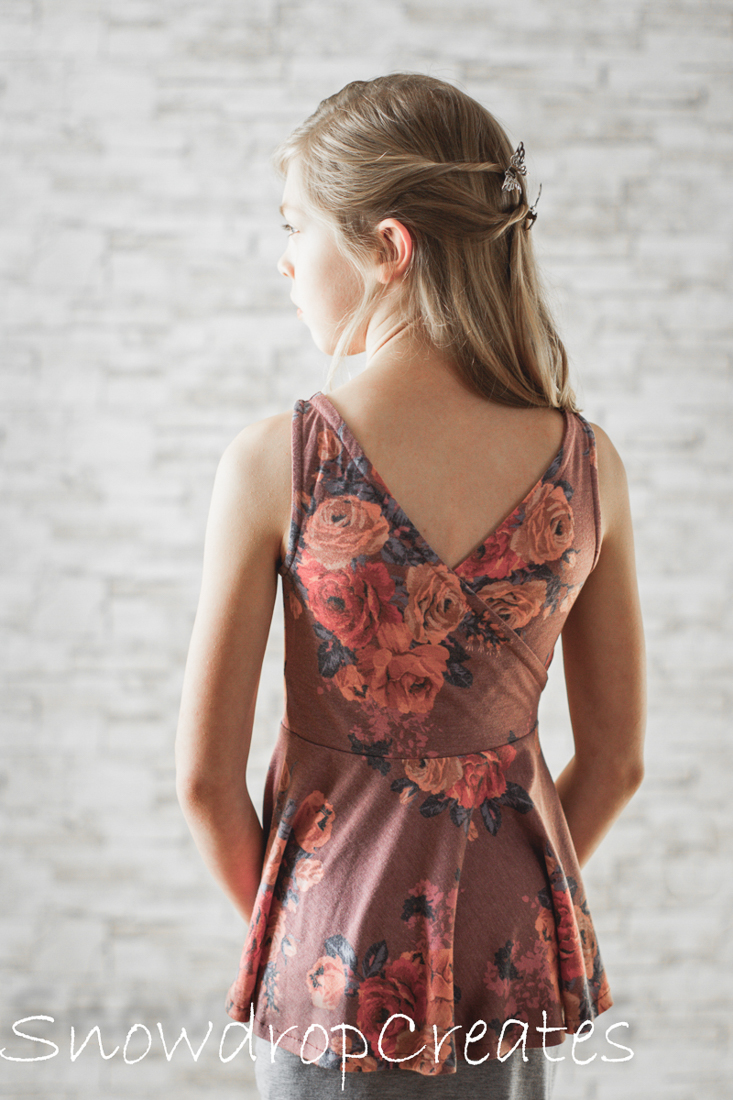 Dandelion Peplum tank with criss cross back and hidden facings for a clean look.