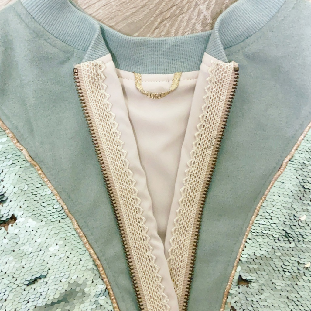 The inside of the Rose Hip bomber jacket with a hanging loop and gorgeous trim over the zipper tape.