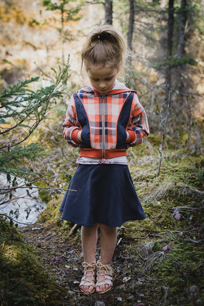 A plaid jacquard jersey Rose Hip jacket with hood and welt pockets and shown with the Spruce skirt.