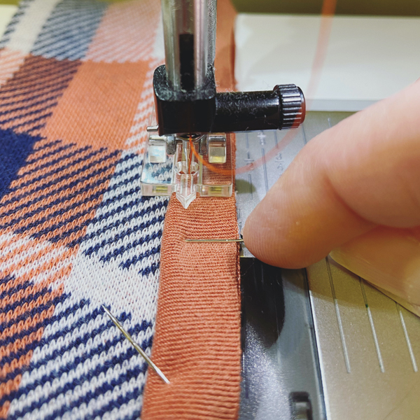 Using an invisible zipper foot to attach satin cording or piping.