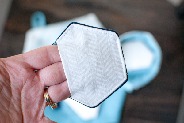 Unique hexagon shaped reusable make-up removing pad with finger hold pocket.