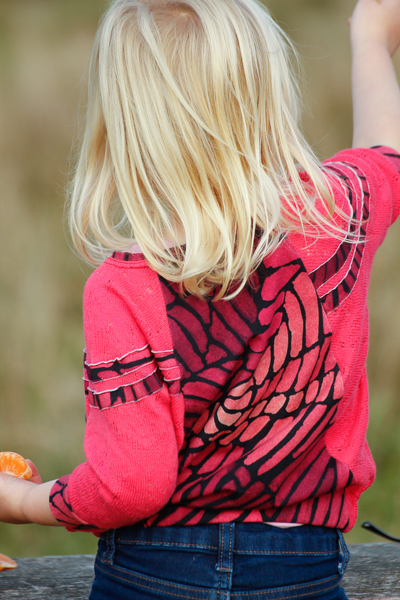 A raglan sweater with batwing sleeves with stripe details in girls' sizes 2-16.
